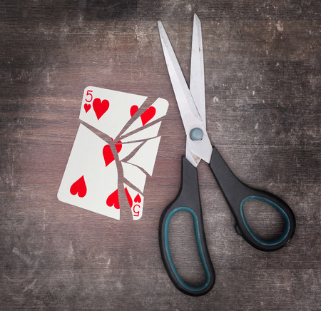 doublet: Concept of addiction, card with scissors, five of hearts
