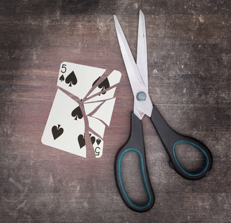 doublet: Concept of addiction, card with scissors, five of spades Stock Photo