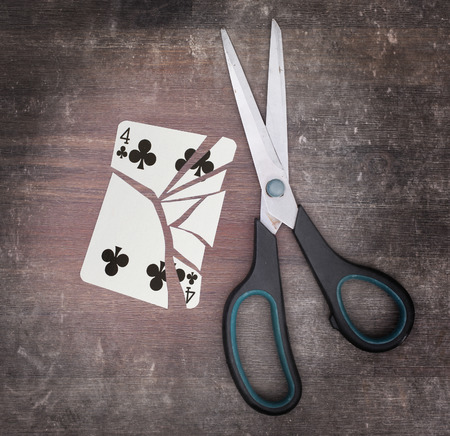 doublet: Concept of addiction, card with scissors, four of clubs Stock Photo