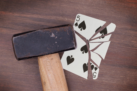 spades: Hammer with a broken card, vintage look, five of spades Stock Photo