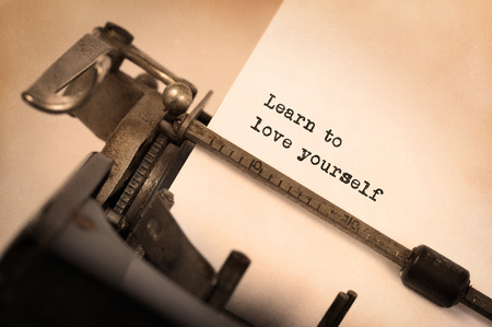 Vintage inscription made by old typewriter, Learn to love yourself Standard-Bild