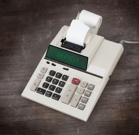 negotiable instrument: Old calculator showing a text on display - deficit Stock Photo