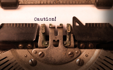 old typewriter: Vintage inscription made by old typewriter, caution Stock Photo