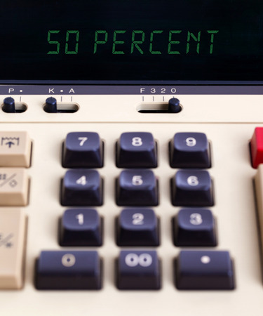 off balance: Old calculator with digital display showing a percentage - 50 percent Stock Photo