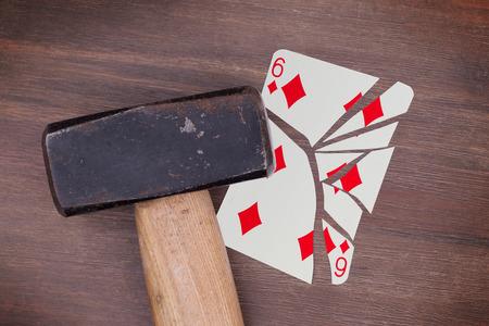 Hammer with a broken card, six of diamonds