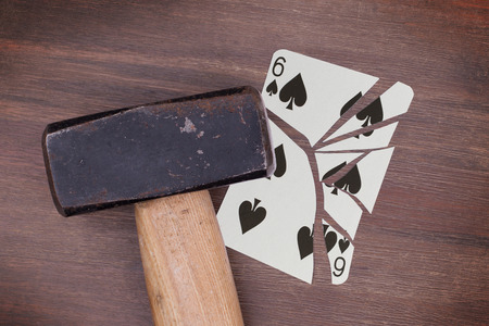 spades: Hammer with a broken card, six of spades Stock Photo