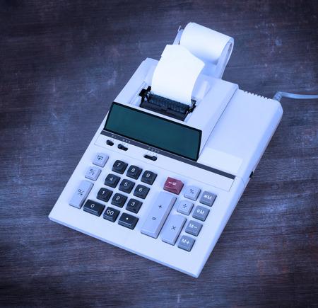old desk: Old dirty calculator on a wooden desk - cold blue filter
