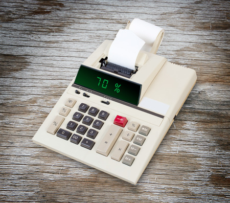 sign equals: Old calculator with digital display showing a percentage - 70 percent Stock Photo