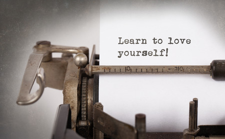 Vintage inscription made by old typewriter, Learn to love yourself Stock Photo