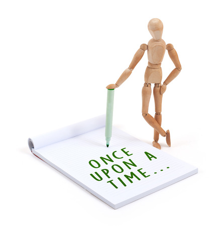 phrase novel: Wooden mannequin writing in a scrapbook - Once upon a time