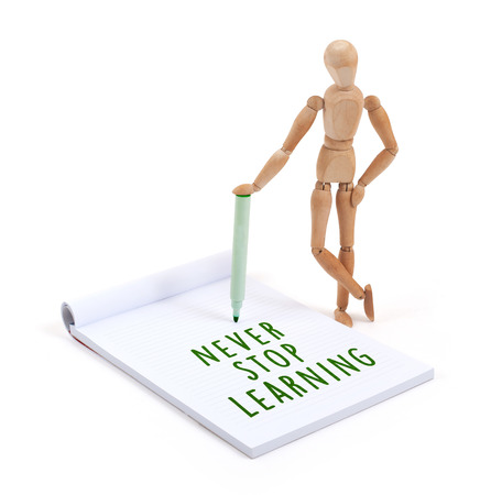 artists dummy: Wooden mannequin writing in a scrapbook - Never stop learning
