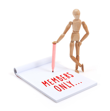 only members: Wooden mannequin writing in a scrapbook - Members only Stock Photo