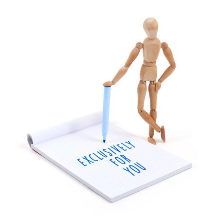 exclusively: Wooden mannequin writing in a scrapbook - XXXXX