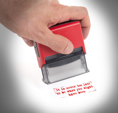 too late: Plastic stamp in hand, isolated on white - It is never too late to be what you might have been
