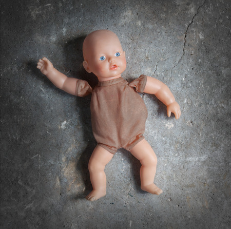 unloved: Abandoned doll laying on a concrete floor
