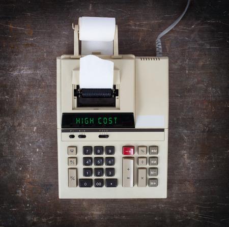 calculadora: Calculadora viejo que muestra un texto en la pantalla - alto costo Foto de archivo