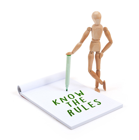 artists dummy: Wooden mannequin writing in a scrapbook - Know the rules Stock Photo