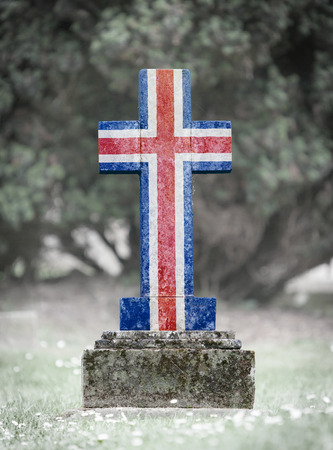 gravestone: Old weathered gravestone in the cemetery - Iceland flag