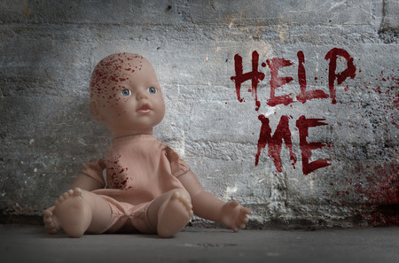 Concept of child abuse - Bloody doll, vintage Stock Photo