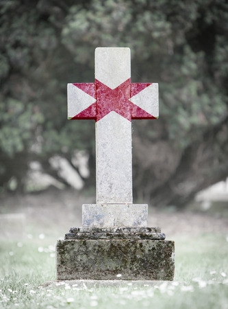 alabama flag: Old weathered gravestone in the cemetery with Alabama flag