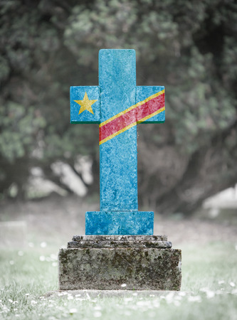 gravestone: Old weathered gravestone in the cemetery with flag of Congo