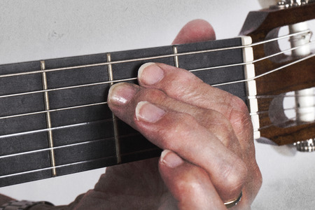 mano anziano: Old hand and guitar isolated on white background