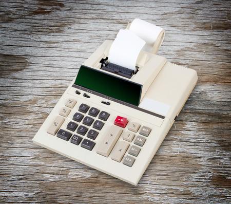 old desk: Old dirty calculator on a wooden desk