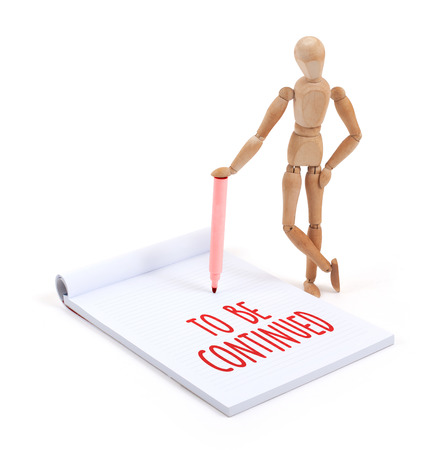 continued: Wooden mannequin writing in a scrapbook - To be continued Stock Photo