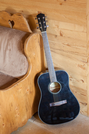 leaning against: Acoustic guitar leaning against an old chair Stock Photo