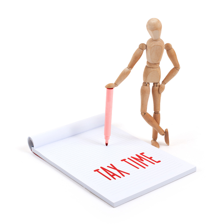 artists dummy: Wooden mannequin writing in a scrapbook - Tax time
