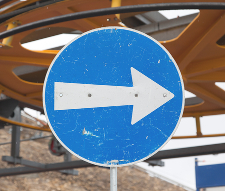 blue arrow: Blue road sign with white arrow pointing right, ski lift in Switzerland