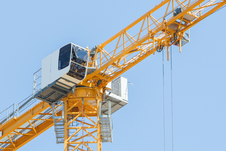 buildingsite: Yellow crane and blue sky on building site Stock Photo