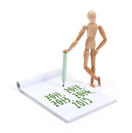 artists dummy: Wooden mannequin writing in a scrapbook - 2015