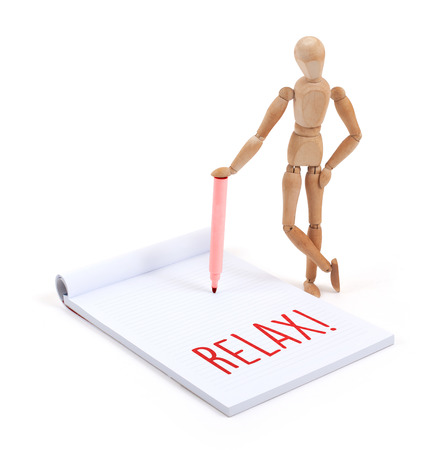 artists dummy: Wooden mannequin writing in a scrapbook - Relax Stock Photo