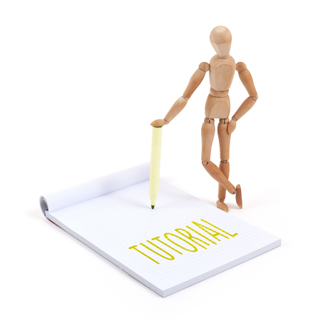 artists dummy: Wooden mannequin writing in a scrapbook - Tutorial Stock Photo