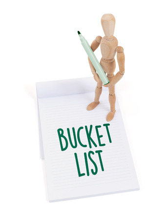 artists dummy: Wooden mannequin writing in a scrapbook - Bucket list Stock Photo