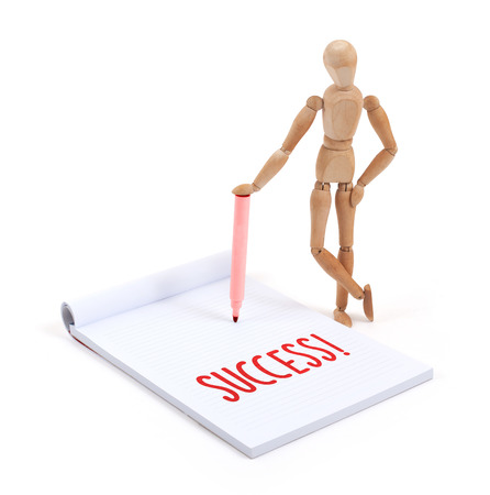 artists dummy: Wooden mannequin writing in a scrapbook - Success Stock Photo