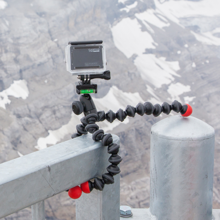 LES DIABLERETS, SWITZERLAND - JULY 22, 2015: Closeup of GoPro Hero 4 camera on GorillaPod tripod in action, filming fast moving clouds. Editorial