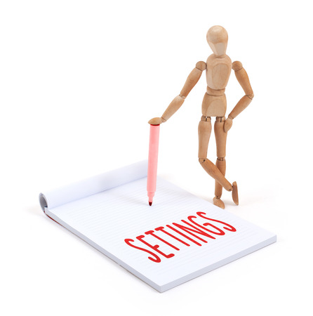 artists dummy: Wooden mannequin writing in a scrapbook - Settings Stock Photo