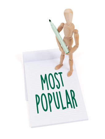 most popular: Wooden mannequin writing in a scrapbook - Most popular