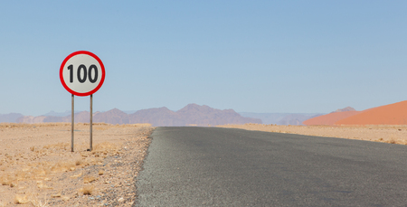 kph: Speed limit sign at a desert road in Namibia, speed limit of 100 kph or mph Stock Photo