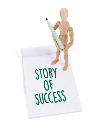 artists dummies: Wooden mannequin writing in a scrapbook - Story of success
