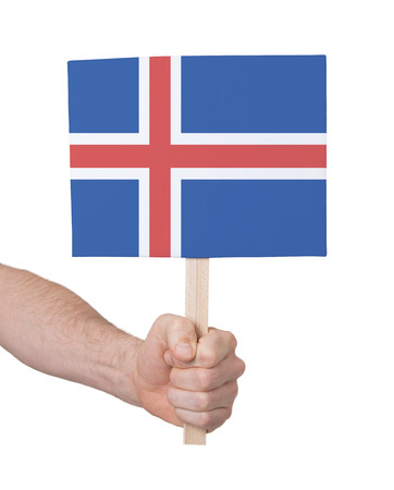 the icelandic flag: Hand holding small card, isolated on white - Flag of Iceland Stock Photo