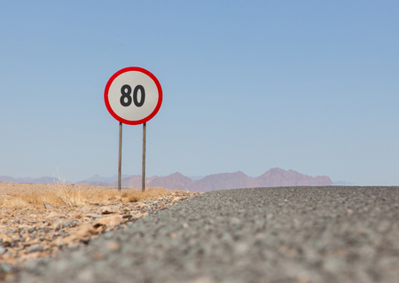 mph: Speed limit sign at a desert road in Namibia, speed limit of 80 kph or mph Stock Photo
