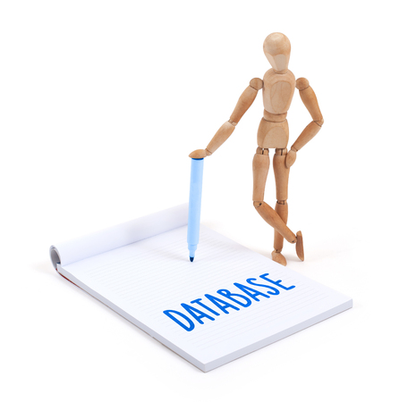 artists dummy: Wooden mannequin writing in a scrapbook - Database Stock Photo
