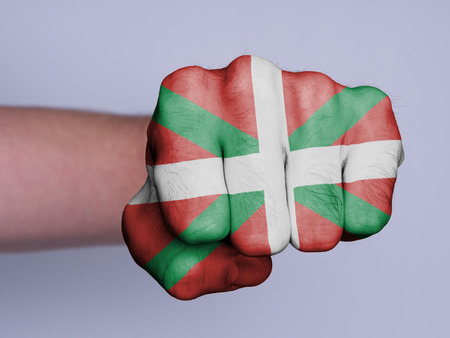 the basque country: Very hairy knuckles from the fist of a man punching, flag of Basque Country