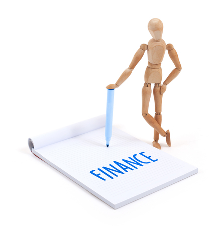 artists dummy: Wooden mannequin writing in a scrapbook - Finance Stock Photo