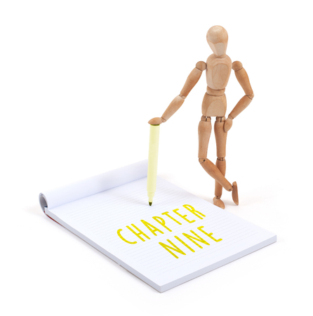 artists dummies: Wooden mannequin writing in a scrapbook - Chapter nine Stock Photo