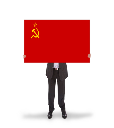 ussr: Smiling businessman holding a big card, flag of the USSR, isolated on white Stock Photo
