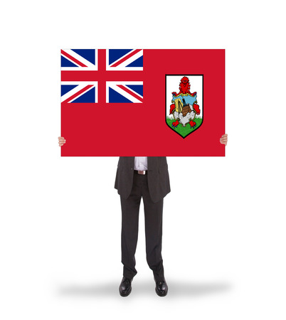 bermuda: Smiling businessman holding a big card, flag of Bermuda, isolated on white